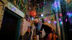 Michel Ayoub, seorang Kristen Arab-Israel, menabuh drum ketika membangunkan kaum muslim untuk sahur di Arce, Israel, Senin (20/6). Michel Ayoub sudah bertahun-tahun membangunkan kaum muslim di sekitarnya untuk sahur selama Ramadan. (REUTERS/Ammar Awad)