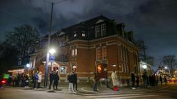 Warga mengantre untuk memberikan suara di luar TPS pada jam terakhir pemungutan suara dalam pemilihan umum di Amsterdam, Belanda, Rabu (17/3/2021). Pemilu digelar selama tiga hari untuk memungkinkan warga memilih dengan aman selama pandemi virus corona COVID-19. (AP Photo/Peter Dejong)