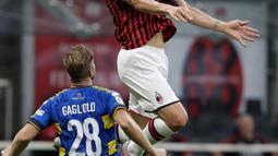 Penyerang AC Milan, Zlatan Ibrahimovic mengontrol bola dari kawalan pemain Parma, Riccardo Gagliolo pada pertandingan lanjutan Liga Serie A Italia di Stadion San Siro di Milan, Italia (15/7/2020). AC Milan menang telak 3-1 atas Parma. (AP Photo/Luca Bruno)
