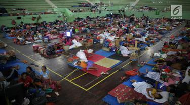 Sejumlah pengungsi Gunung Agung berisitirahat di lokasi pengungsian GOR Swecapura, Klungkung, Bali, Minggu (3/12). Pengungsi Gunung Agung yang berada di Kabupaten Klungkung terus bertambah dengan total 9.304 jiwa. (Liputan6.com/Immanuel Antonius)