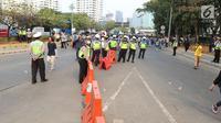 Polisi mengawal mahasiswa yang akan melangsungkan demonstrasi menolak RUU KUHP dan revisi UU KPK di Gedung DPR, Jakarta, Selasa (24/9/2019). Demonstrasi mahasiswa berbimbas pada macetnya Tol Dalam Kota. (Liputan6.com/Herman Zakharia)