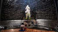 Seorang wanita berdoa untuk mengenang setahun tragedi bom gereja Surabaya di Gereja Katolik Santa Maria, Surabaya, Jawa Timur, Senin (13/5/2019). Pada peringatan tersebut digelar juga doa lintas agama yang dihadiri sejumlah pemuka agama. (Juni Kriswanto/AFP)