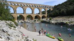 Wisatawan bermain kayak di dekat Pont du Gard atau Jembatan Gard di Vers-Pont-du-Gard, Prancis, Rabu (21/8/2019). Pont du Gard dibangun oleh Marcus Vipsanius Agrippa menantu dari Caesar Augustus. (Pascal GUYOT/AFP)