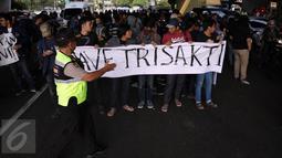 Anggota polisi mengamankan aksi protes mahasiswa Universitas Trisakti yang menutup Jalan Kyai Tapa, Jakarta Barat, Jumat (2/9). Aksi itu mendesak penyelesaian kisruh masalah internal antara rektorat dengan yayasan kampus. (Liputan6.com/Johan Tallo)