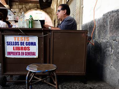 Seorang notaris saat bekerja menulis dokumen di Santo Domingo Square, Meksiko, (23/8). Notaris yang berada di pinggir jalan ini menerima jasa menulis surat terkait hukum perdata, lamaran kerja, wasiat, bahkan surat cinta. (AFP PHOTO/ALFREDO ESTRELLA)