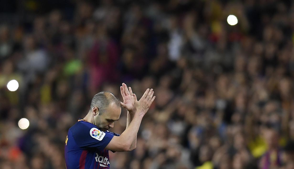 Gelandang Barcelona, Andres Iniesta, menyapa suporter usai melawan Real Madrid pada laga La Liga Spanyol di Stadion Camp Nou, Barcelona, Minggu (6/5/2018). Sepanjang karier dirinya mempersembahkan 32 trofi untuk La Blaugrana. (AFP/Lluis Gene)