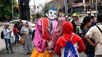 Foto pada 16 Maret 2019 menunjukkan ondel-ondel yang dioperasikan oleh seorang anak untuk mengamen di jalanan Jakarta. Seiring berjalan waktu, ondel-ondel yang dahulu sebagai ikon kesenian Betawi kini mudah ditemui di sejumlah jalan dan gang-gang di antara permukiman warga. (GOH CHAI HIN / AFP)