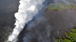 Pemandangan saat lava pijar Gunung Kilauea mengalir ke laut di dua lokasi dekat Pahoa, Hawaii, Amerika Serikat, Minggu (20/5). (Survei Geologi AS via AP)