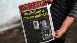 Seorang pria menunjukkan koran yang berisi berita tewasnya wartawan Leobardo Vazquez di Gutierrez Zamora, Meksiko (22/3). Vazquez adalah wartawan ketiga yang dibunuh di Meksiko tahun ini. (AP/Felix Marquez)