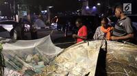 Pencari suaka mendirikan tenda untuk beristirahat di atas trotoar depan kantor UNHCR, Jalan Kebon Sirih, Jakarta, Jumat (5/7/2019). Para pencari suaka ini membangun tenda-tenda dan meminta kepastian perlindungan dari UNHCR . (Liputan6.com/Helmi Fithriansyah)