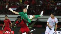 Bek Timnas Indonesia, Yanto Basna, berebut bola dengan kiper Timnas Vietnam, Dang Van Lam, pada laga Kualifikasi Piala Dunia 2022 di Stadion Kapten I Wayan Dipta, Bali, Selasa (15/10). Indonesia kalah 1-3 dari Vietnam. (AFP/Aditya Wany)