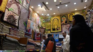 Jemaah haji memilih sajadah yang dipajang di sebuah toko di kota suci Makkah, Arab Saudi pada Selasa (6/8/2019). Puncak Ibadah haji masih beberapa hari lagi, namun jemaah sudah memborong aneka barang antara lain tasbih, baju, teko emas, kurma, sajadah, minyak wangi dan lainnya. (FETHI BELAID/AFP)