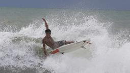 Abu Dzar Al-Ghifari berselancar di lepas pantai Carita, Banten (26/12). Pemerintah meminta warga menghindari pantai di daerah-daerah tersebut di mana tsunami telah menewaskan 420 jiwa akhir pekan lalu. (AP Photo/Achmad Ibrahim)