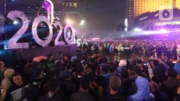 Warga berkerumun menikmati salah satu panggung hiburan di Bundaran Hotel Indonesia, Jakarta, Selasa (31/12/2019). Meski Jakarta diguyur hujan sejak Selasa (31/12) sore, warga tetap antusias melewati malam pergantian tahun 2019 menuju 2020 di kawasan Bundaran HI Jakarta. (Liputan6.com/Angga Yuniar)