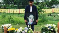 Husni Fadhil berdiri di samping makam kekasihnya yang merupakan pramugari Lion Air JT 610. (dok. Instagram @apryfadhil/https://www.instagram.com/p/Bp9KPn6gIIv/?utm_source=ig_web_copy_link/Asnida Riani)