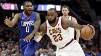 LeBron James (23) menggiring bola melewati adangan pemain Los Angeles Clippers, Sindarius Thornwell (0) pada laga NBA basketball game di Quicken Loans Arena, Cleveland, (18/11/2017), Cavs menang 118-113. (AP/Tony Dejak)