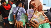 Warga menunjukkan uang dan tinta di jari tanda sudah menukar uang pecahan di mobil layanan kas keliling di Malang pada Mei, 2018 (Liputan6.com/Zainul Arifin)