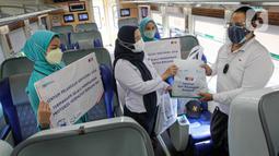 Petugas memberikan bingkisan kepada penumpang KA Taksaka di Stasiun Gambir, Jakarta, Sabtu (4/8/2021). Dalam rangka memperingati hari pelanggan nasional, PT KAI Daop 1 Jakarta membagikan ratusan bingkisan kepada penumpang kereta api. (Liputan6.com/Faizal Fanani)
