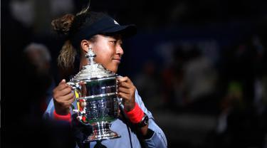 Petenis Jepang, Naomi Osaka memegang trofi turnamen AS Terbuka setelah mengalahkan petenis AS, Serena Williams pada partai final di Arthur Ashe Stadium, New York, Sabtu (8/9). Naomi Osaka menang dua set dengan skor 6-2 dan 6-4. (AP/Adam Hunger)