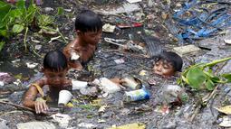 Sejumlah anak memilah sampah yang terapung untuk di jadikan bahan daur ulang di sebuah sungai yang tercemar di kota navotas, Manila, Kamis (2/7/2015). Daur ulang bertujuan untuk mengurangi tingkat pencemaran sungai. (REUTERS/Romeo Ranoco)
