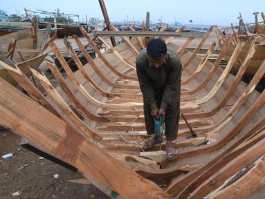 Tukang kayu Pakistan membuat kapal penangkap ikan di sebuah pelabuhan di Karachi (3/4). Pembuatan kapal buatan Pakistan menghasilkan ratusan kapal setiap tahun untuk memenuhi permintaan industri perikanan setempat. (AFP Photo/Asif Hassan)