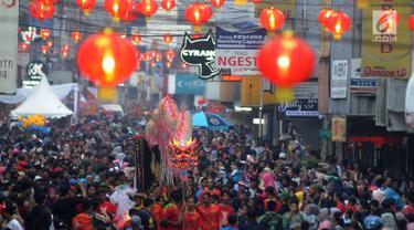 Warga memadati jalan raya saat arak-arakan atraksi liong perayaan Cap Go Meh melewati Jalan Suryakencana, Bogor, Jawa Barat, Selasa (19/2). Acara ini merupakan puncak perayaan Tahun Baru Imlek 2570. (Merdeka.com/Arie Basuki)