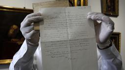 """Petugas rumah lelang Winner menunjukkan surat rumusan """"Tahap Ketiga Teori Relativitas"""" yang ditulis oleh Albert Einstein di Yerusalem, Selasa (6/3). Surat resmi tulisan tangan itu dikirim dari Berlin pada 1928 untuk ahli matematika. (MENAHEM KAHANA/AFP)"""