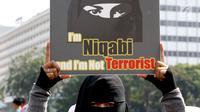 Anggota komunitas  Niqab Squad menunjukan poster saat melakukan Challenge kepada pengunjung CFD untuk mengenakan Niqab di kawasan Bundaran HI, Jakarta, Minggu (10/9). (Liputan6.com/Johan Tallo)