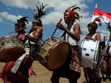 Warga menggebuk drum dalam upacara penyambutan peresmian bantuan bedah rumah di Desa Oebelo, Kupang, NTT, Selasa (14/8). Upacara penyambutan tersebut diwarnai dengan tarian-tarian menggunakan alat musik baba khas daerah itu. (Liputan6.com/Johan Tallo)
