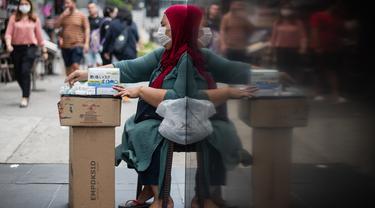 Seorang wanita menjual masker di tengah kekhawatiran akan penyebaran virus corona COVID-19, di Kuala Lumpur, Malaysia, Kamis, (13/2/2020). WHO kini tidak lagi menyebut virus yang merebak di China sebagai Virus Corona Baru. (AFP/Mohd Rasfan)