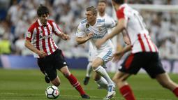 Pemain Real Madrid, Toni Kroos (tengah) mencoba menerobos pertahanan Athletic Bilbao pada lanjutan La Liga Santander di Santiago Bernabeu stadium, Madrid, (18/4/2018). Real Madrid bermain imbang 1-1 dengan Bilbao. (AP/Francisco Seco)