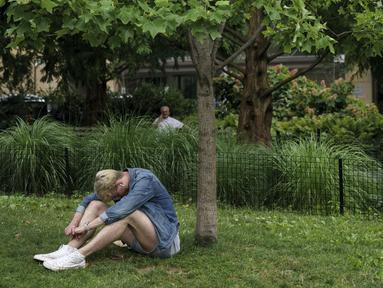 Seorang pria duduk di tempat teduh saat siang hari yang panas di Washington Square Park di New York City (17/7/2019). Panas terik bergerak ke daerah Kota New York, dengan suhu yang diperkirakan akan mencapai 100 derajat pada akhir pekan ini.  (AFP Photo/Drew Angerer)