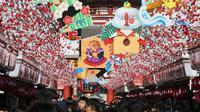 Pejalan kaki melintas di bawah dekorasi shio babi tanah yang mengarah ke kuil Buddha Asakusa Sensoji di Tokyo, Jepang, Kamis (27/12). Tahun 2019 masuk ke dalam shio babi tanah. (AP Photo/Koji Sasahara)
