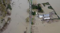Jalanan yang tertutup air mengganggu kendaraan yang akan melintasi kawasan dekat sungai Snoqualmie, Washington, Kamis (19/11/2015). Bencana ini menewaskan sedikitnya tiga orang. (REUTERS / David Ryder)