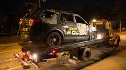Mobil polisi Georgia berada di atas truk setelah dibakar pengunjuk rasa di depan kantor polisi di kampus di Atlanta, AS (18/9). Akibat kejadian ini dua petugas luka ringan, dengan satu dibawa ke rumah sakit untuk perawatan. (Foto AP / Kevin D. Liles)