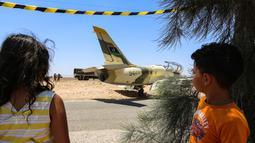 Dua anak melihat kondisi pesawat jet tempur Libya L-39 Albatros pasukan Khalifa Haftar di Kota Medenine di perbatasan Tunisia-Libya (22/7/2019). Jet tempur yang sedang melakukan misi pengintaian dan patroli itu mengalami masalah teknis yang mengakibatkan pendaratan darurat di jalan raya. (AFP Photo/