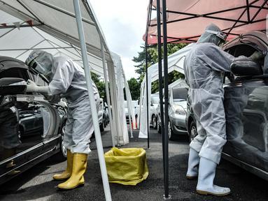 Petugas kesehatan melakukan tes usap PCR drive thru kepada pengguna kendaraan di halaman Rumah Sakit Pertamina Jakarta (RSPJ), Rabu (6/1/2021). RSPJ menyediakan layanan tes usap PCR mandiri secara drive thru guna melacak sekaligus memutus penyebaran Covid-19. (merdeka.com/Iqbal Nugroho)