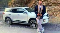 Mantan pegulat WWE Great Khali berpose di sebelah Toyota Fortuner. (Cartoq)