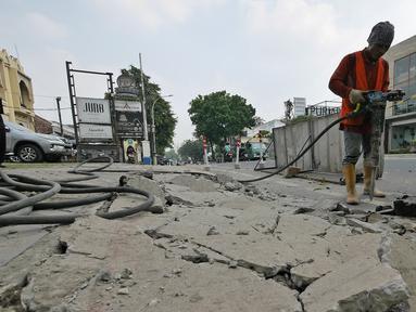Pekerja menyelesaikan proyek revitalisasi trotoar di kawasan Kemang, Jakarta, Jumat (29/6/2019). Revitalisasi trotoar Kemang ditargetkan selesai pada November 2019. (Liputan6.com/Herman Zakharia)