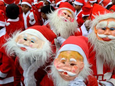 Anak-anak sekolah India mengenakan kostum Santa Claus berpose saat mereka mengambil bagian dalam acara Natal di sebuah sekolah di Chennai, (5/12). Natal adalah hari raya umat Kristen yang diperingati setiap tanggal 25 Desember. (AFP Photo/Arun Sankar)