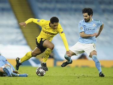 Pemain Manchester City, Phil Foden, menghadang pemain Borussia Dortmund, Jude Bellingham, pada laga Liga Champions di Stadion Etihad, Rabu (7/4/2021). City menang dengan skor 2-1. (AP/Dave Thompson)
