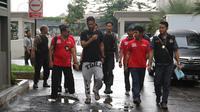 Seorang WNA dibawa petugas untuk menjalani tes urine ketika razia di Apartemen Kalibata City, Jakarta, Kamis (25/2). Ratusan petugas gabungan melakukan razia dalam rangka mengantisipasi peredaran dan penyalahgunaan narkoba. (Liputan6.com/Herman Zakharia)