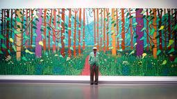 Pelukis asal inggris David Hockney berpose di depan lukisan besarnya di Perpustakaan Pompidou Center, Paris, Perancis, Selasa (26/9). Lukisan ini mencakup 32 panel dengan tinggi 3 meter dan lebar hampir 10 meter. (Foto AP/Francois Mori)