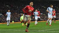 Striker Manchester United Alexis Sanchez merayakan gol kedua untuk timnya saat melawan Huddersfield Town dalam pertandingan Liga Inggris di Old Trafford di Manchester (3/2). (AFP Photo/Paul Ellis)