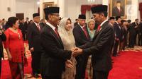 Presiden Joko Widodo atau Jokowi (kanan) bersalaman dengan mantan Menko Polhukam Wiranto usai dilantik sebagai Dewan Pertimbangan Presiden (Wantimpres) di Istana Negara, Jakarta, Jumat (13/12/2019). Wiranto ditunjuk sebagai ketua merangkap anggota Wantimpres. (Liputan6.com/Angga Yuniar)