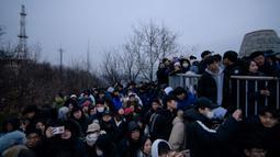 Orang-orang berkumpul di sudut pandang yang menghadap ke cakrawala kota untuk menyaksikan matahari terbit pertama tahun baru, meskipun dalam kondisi mendung, di Seoul, Korea Selatan (1/1/2020). (AFP/Ed Jones)