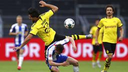 Pemain Borussia Dortmund, Emre Can, berebut bola dengan pemain Hertha Berlin, Vladimir Darida, pada laga Bundesliga di Stadion di Signal Iduna Park, Sabtu (6/6/2020). Borussia Dortmund menang 1-0 atas Hertha Berlin. (AP/Lars Baron)