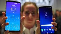 Seorang model menunjukkan ponsel Samsung Galaxy S9 Plus dan Samsung Galaxy S9 saat acara Samsung Galaxy S9 Unpacked di Barcelona, Spanyol (25/2). (AFP Photo/Lluis Gene)