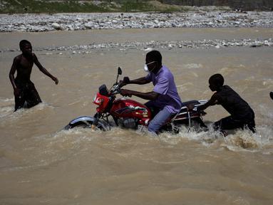 Bocah laki-laki membantu pengendara sepeda motor yang berusaha menyeberangi sungai di Les Anglais, 10 Oktober 2016. Selain merusak ribuan rumah, badai Matthew di Haiti juga memutus jembatan yang biasa digunakan warga. (REUTERS/Andres Martinez Casares)
