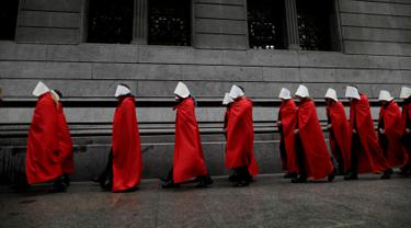 Aktivis yang mendukung dekriminalisasi aborsi berjalan di luar Kongres, Buenos Aires, Argentina, Rabu (25/7). Para aktivis mengenakan jubah merah dan topi putih seperti tokoh dalam serial televisi 'The Handmaid's Tale'. (AP Photo/Natacha Pisarenko)